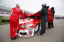 Chip Ganassi Racing crew members remove the covers after rain