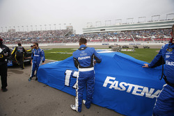Roush Fenway Racing crew members remove the covers after rain