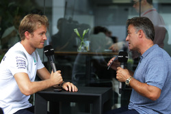 (L to R): Nico Rosberg, Mercedes AMG F1 with Jean Alesi, Canal+ Presenter