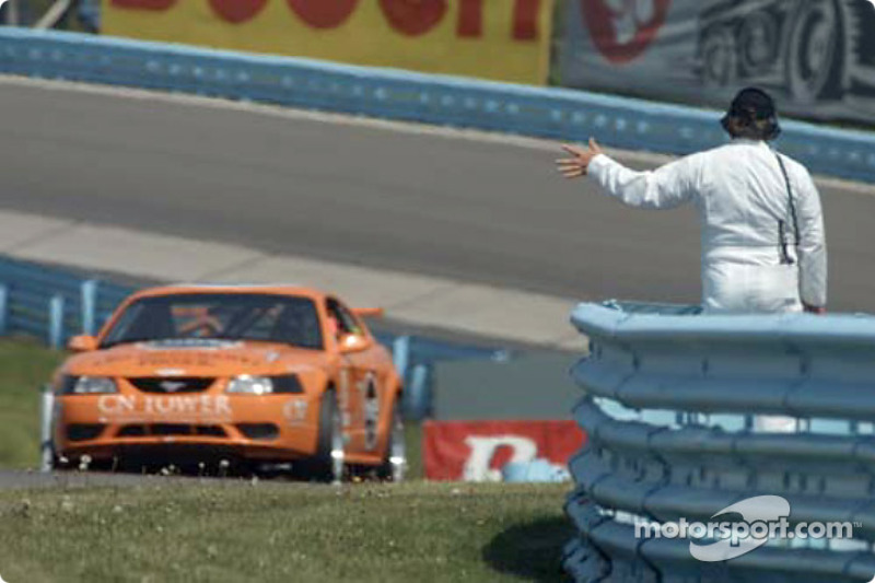 The Doncaster Racing Mustang Cobra is waved to by a corner work