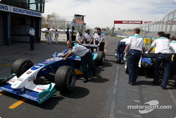 Sauber crew members push the cars to the Parc Fermé
