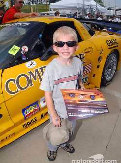 A young fan shows off the hero card he received from Corvette Racing during the fan pitwalk