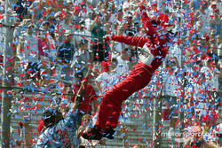 Helio Castroneves does the Superman routine and climb the fence in celebration