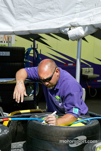 An un-named crew member marks tires before Friday's practice session