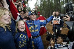 Petter Solberg celebrates with fans at the stop control of the final stage