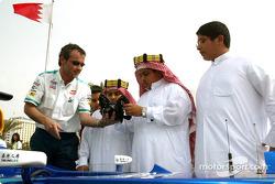 Sauber team member demonstrates steering wheel to fans