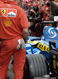 Ferrari team members inspect the Renault F1