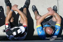 Team members rest on pitlane