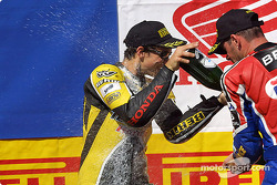 Chris Vermeulen gets sprayed with champagne by Regis Laconi