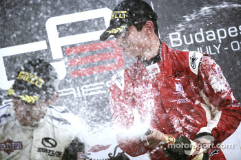 Alexander Rossi celebrates victory on the podium with Robert Wickens