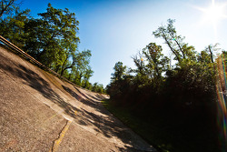 The banking and rusted guard rail on the old circuit