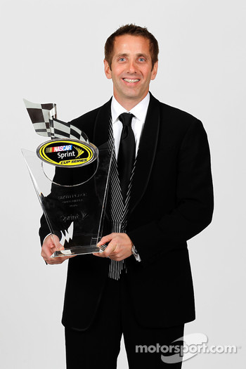 NASCAR driver Greg Biffle poses with his sixth place trophy