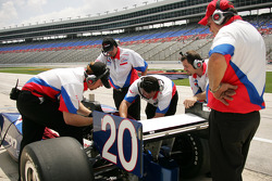 Crew members work on the car of Ed Carpenter