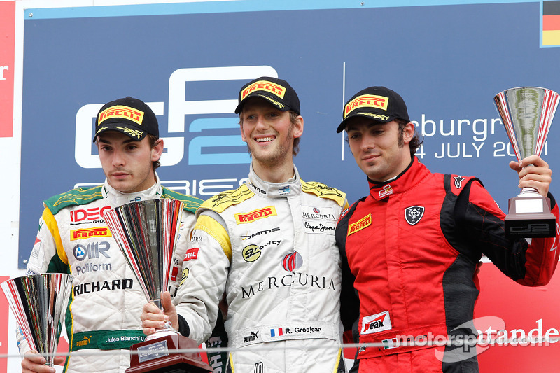 Romain Grosjean celebrates his victory on the podium with Jules Bianchi and Luca Filippi