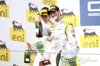 Romain Grosjean celebrates his fifth feature race win of the season on the podium with Charles Pic