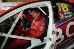 Darrell Waltrip sits with a steering wheel on the passenger side of the Brad Jones Racing V8 Supercar of Jason Bright