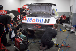 Stewart-Haas Racing Chevrolet team members work hard to repair the car of Tony Stewart
