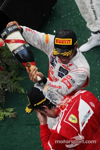 Second placed Sergio Perez celebrates with champagne with race winner Fernando Alonso, Ferrari