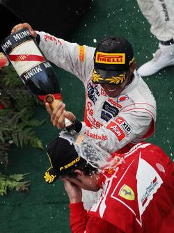 Second placed Sergio Perez celebrates with champagne with race winner Fernando Alonso, Ferrari