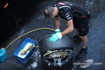 A Lotus F1 Team mechanic cleaning tyres