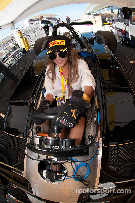 A lovely Pirelli girl tries out a vintage F1 car