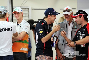 Sebastian Vettel, Red Bull Racing, Michael Schumacher, Mercedes AMG F1 and Timo Glock, Marussia F1 Team enjoy something on a mobile phone