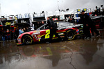 The car of Jeff Gordon, Hendrick Motorsports Chevrolet being pushed in the rain
