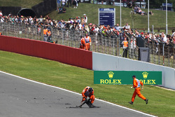 Marshals come on to the track to remove debris from the circuit