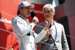 Race winner Nico Rosberg Mercedes AMG F1 on the podium with Damon Hill Sky Sports Presenter