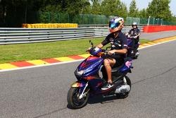 Daniel Ricciardo, Scuderia Toro Rosso STR8 rides the circuit on a moped.