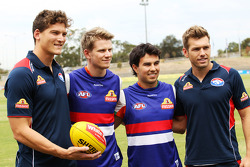 Will Minson, Western Bulldogs Australian Rules Footballer, and Shaun Higgins, Western Bulldogs Australian Rules Footballer, present team jerseys to Nico Hulkenberg, Sahara Force India F1, and team mate Sergio Perez, Sahara Force India F1, at Whitten Oval