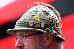 A fan with badges in his hat