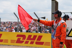 A marshal waves a red flag as the race is stopped