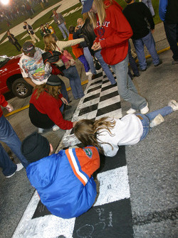 Fans write messages on the start/finish line