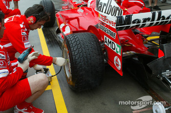 Ferrari team members check tire pressure on the Ferrari of Rubens Barrichello