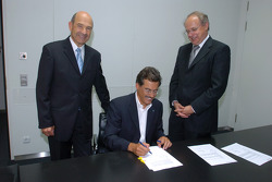 Dr Mario Theissen (BMW Motorsport Director) Peter Sauber, and Prof Burkard Goeschel (Board member for Development BMW Group) sign the contract