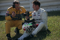 A safety crew member talks to Daniel Colembie after his crash