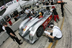 Frank Biela sits the new Audi R10 while crew members work on the car