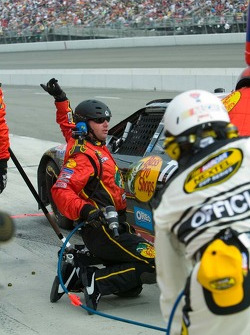 A crewman signals he has completed service during a pit stop for Martin Truex Jr