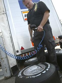 Racing Engineering team member inspects tyres