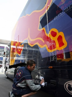 A Red Bull Racing truck cleaned by a crew member
