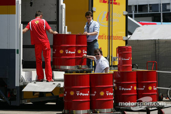 Ferrari team member unloads Shell fuel barrels