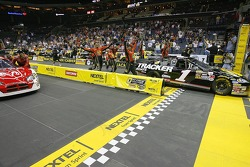The crew of the #1 Bass Pro Shops Chevrolet crosses the finish line ahead of the #9 Dodge Dealers/UAW Dodge to win the NASCAR Nextel Pit Crew Challenge