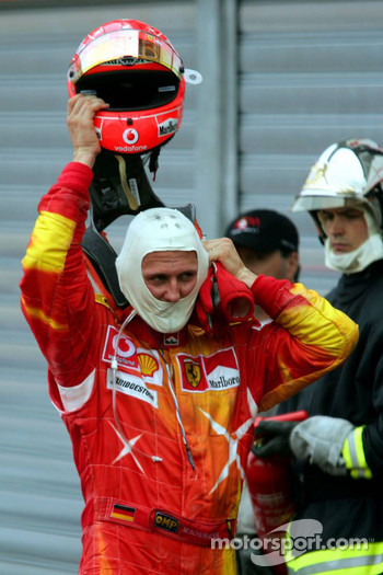 Michael Schumacher takes his helmet off
