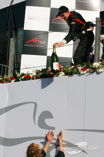 Nico Hulkenberg handing the champaign bottle to his mechanics