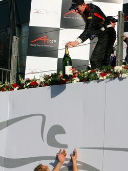 Nico Hulkenberg handing the champaign bottle to his mechanics