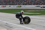 A crew member for David Gilliland retrieves a loose tire