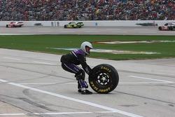 A crew member for David Gilliland retrieves a loose tire