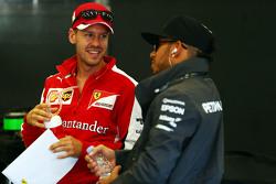 (L to R: Sebastian Vettel, Ferrari with Lewis Hamilton, Mercedes AMG F1