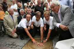The winners of the 24 Hours of Le Mans 2006 Marco Werner, Frank Biela and Emanuele Pirro put their hands on the traditional winners manhole cover in downtown Le Mans